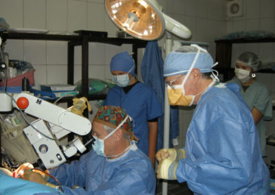 Dr. Brock's Team Performing Surgery with Microscope