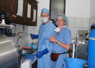 Steve Horan, Assistant, at Work Washing Instruments with Heather Horan, RN, Stopping by to ask How Much Longer on the Autoclave!