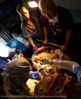 With electricity out, patients are examined with a battery powered light normally used for taking pictures