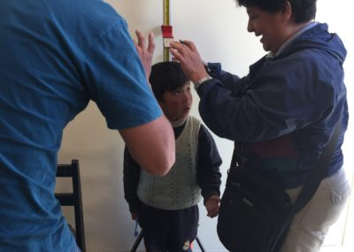 Miguel of the Clinic and Lourdes Measuring the Height of a Child