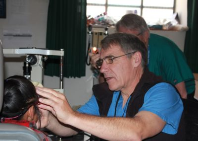 Dr. Paul Schultz Performing an Eye Exam on a Child